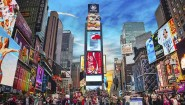 """NEW YORK CITY - MAY 11: Times Square with tourists on May 11, 2013. Iconified as """"The Crossroads of the World"""" it's the brightly illuminated hub of the Broadway Theater District."""