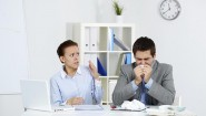 Image of sick businessman sneezing while anxious female looking at him in office