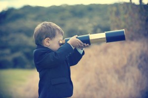 Young boy in a business suit with telescope. Small child wearing a full suit and holding a telescope. He is holding the telescope up to his eye. Business forecasting, innovation, leadership and planning concept. Shot outdoors with trees and grass in the background