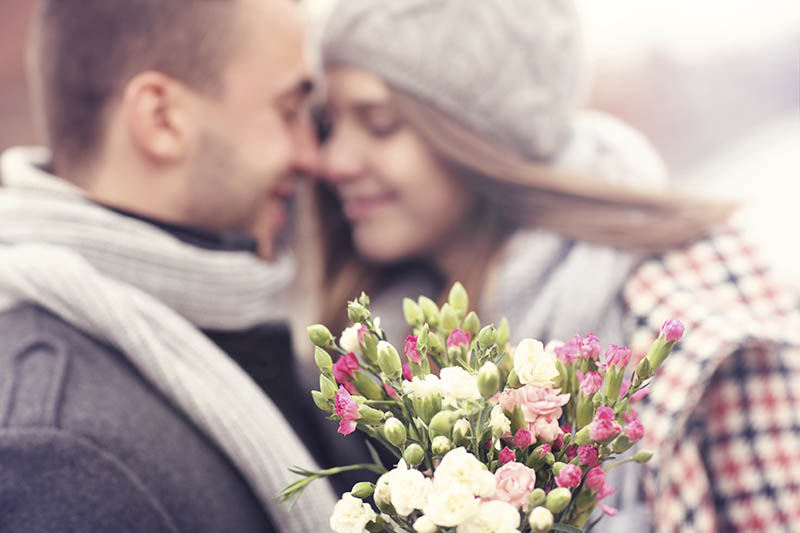 A picture of flowers and kissing couple in the background
