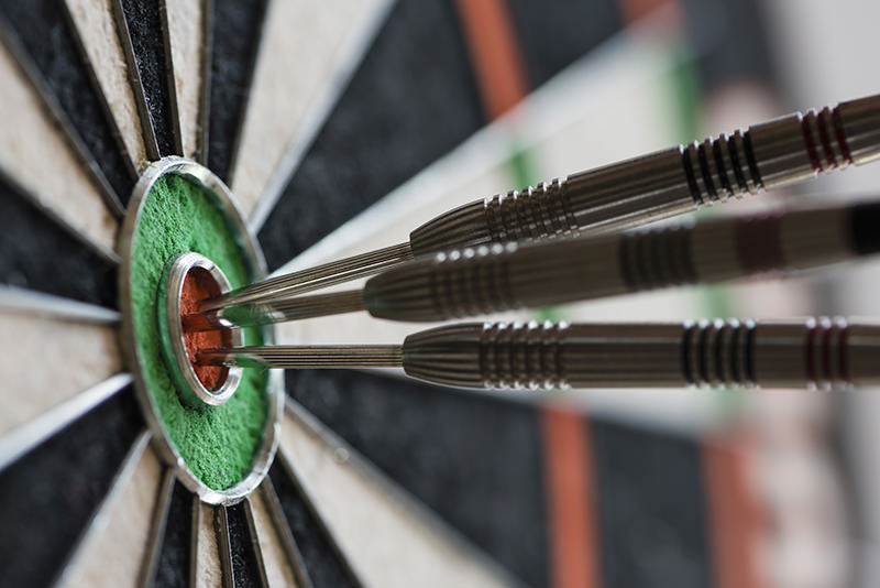 Closeup view of silhouette of three darts sticking in a professional sisal dartboard. All three darts hit the inner bull / bull's eye / mark.
