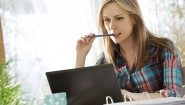 Woman biting pen looking at laptop