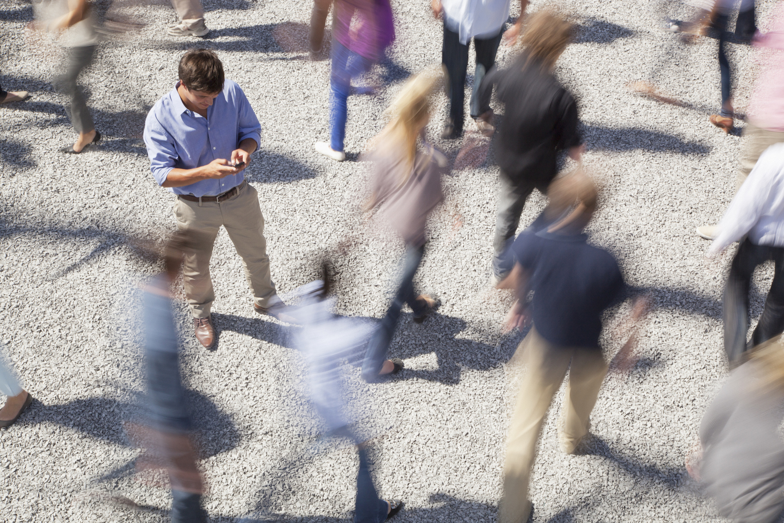 Man checking cell phone among rushing crowd